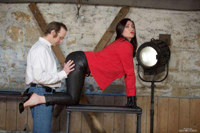 Miss Hybrid sexy leather trousers and gloves with high heels in the dungeon.